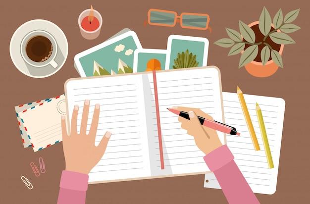 Kobiet ręki trzyma pióro i pisze w dzienniczku. indywidualne planowanie i organizacja. miejsce pracy