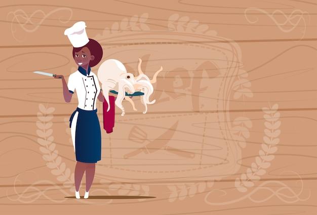 Kobieta african american chef cooka gospodarstwa ośmiornicy cartoon szefa w restauracji jednolite nad drewnianym teksturą tle
