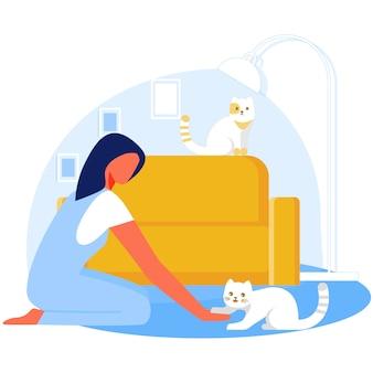 Kobieta bawić się z kotem w żywym pokoju, relaksuje.