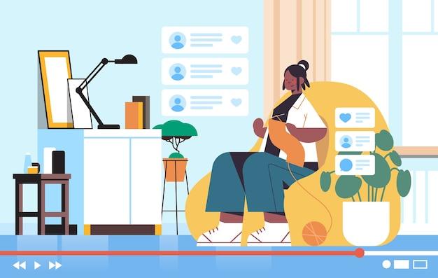 Kobieta blogerka dziewiarska szalik nagrywanie online blog wideo transmisja strumieniowa na żywo koncepcja blogowania afroamerykanin dziewczyna vlogger salon wnętrze poziome
