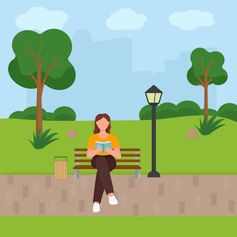 Kobieta czytająca książkę w parku.
