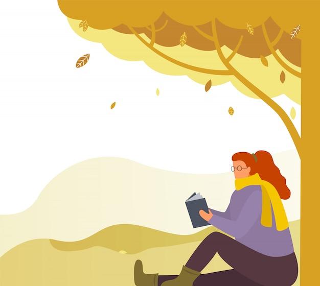 Kobieta czytania literatury w parku jesień