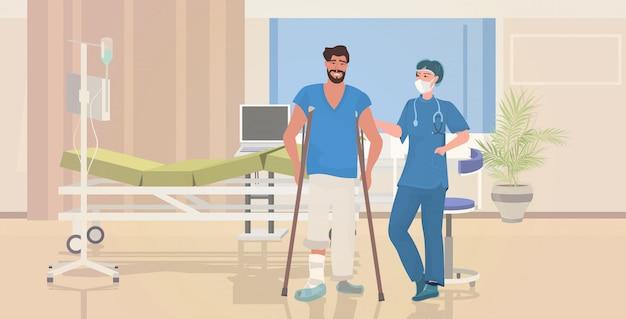 Kobieta doktorski pomaga męski pacjent z złamaną nogą