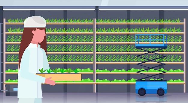 Kobieta inżynier rolnictwa w jednolitym gospodarstwie rośliny doniczkowe nowoczesne organiczne pionowe gospodarstwo rolne wnętrze rolnictwo koncepcja poziomej portret