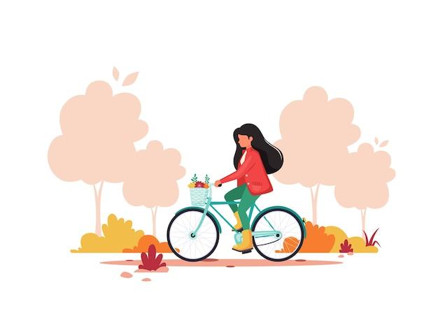 Kobieta, jazda na rowerze w parku jesień. zdrowy styl życia, koncepcja aktywności na świeżym powietrzu.