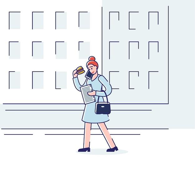 Kobieta je kanapkę i rozmawia przez telefon spacerując ulicą w godzinach porannych.
