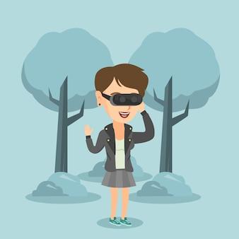 Kobieta jest ubranym rzeczywistości wirtualnej słuchawki w parku.