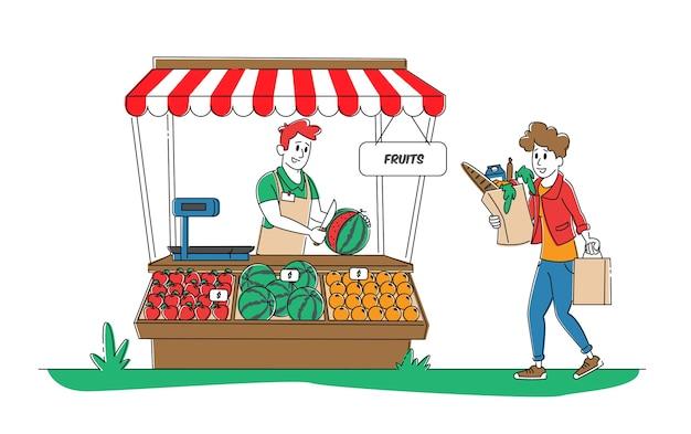 Kobieta kupująca stoi przy biurku z kioskiem z owocami rolnika