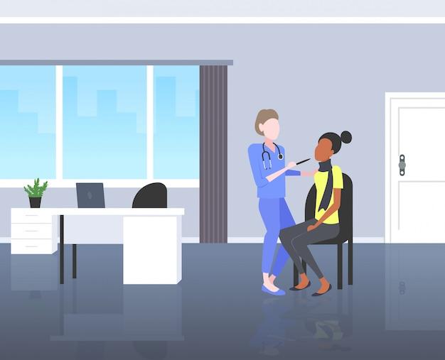 Kobieta lekarz bada gardło afroamerykanka pacjent przez depresora ból medycyny pojęcie opieki zdrowotnej nowoczesny pokój szpitalny wnętrze poziome pełnej długości