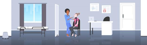 Kobieta lekarz bada gardło kobiety pacjenta przez depresor ból medycyny pojęcie opieki zdrowotnej nowoczesny pokój szpitalny wnętrze poziome pełnej długości