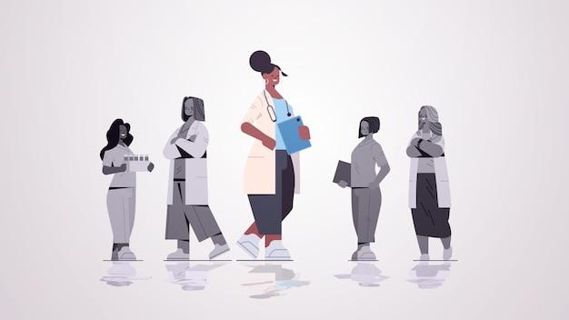 Kobieta lekarz lider stoi przed zespołem lekarzy w jednolitej medycyny koncepcji opieki zdrowotnej poziomej pełnej długości ilustracji wektorowych