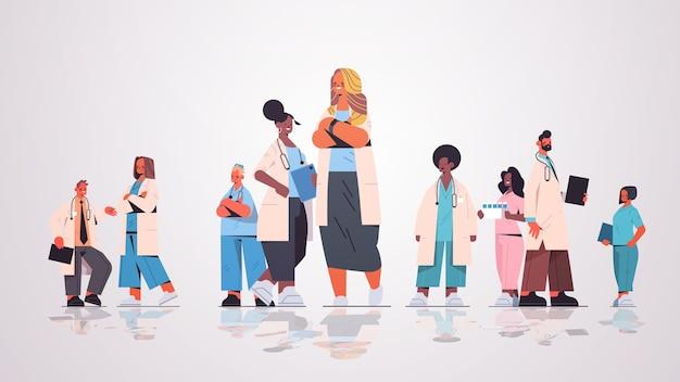 Kobieta lekarz lider stojący przed zespołem specjalistów medycznych rasy mieszanej w jednolitej medycyny koncepcji opieki zdrowotnej poziomej pełnej długości ilustracji wektorowych