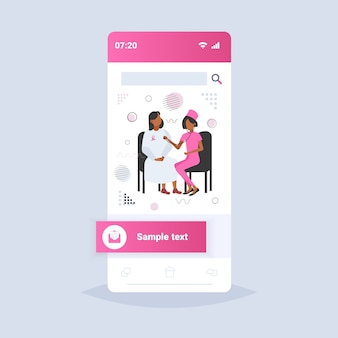 Kobieta lekarz słucha klatki piersiowej afroamerykańskiego pacjenta ze stetoskopem świadomości raka piersi i zapobiegania chorobom