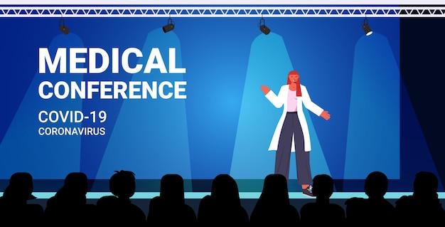Kobieta lekarz wygłasza przemówienie na konferencji medycznej pandemii koronawirusa medycyna koncepcja opieki zdrowotnej wykład sala wnętrze poziome ilustracji wektorowych