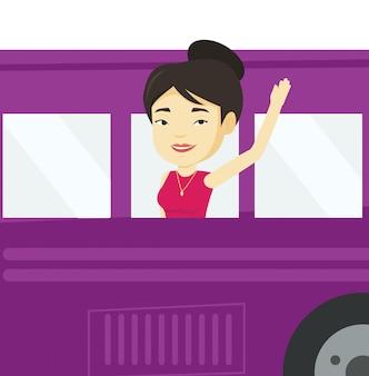 Kobieta macha ręką z okna autobusu.