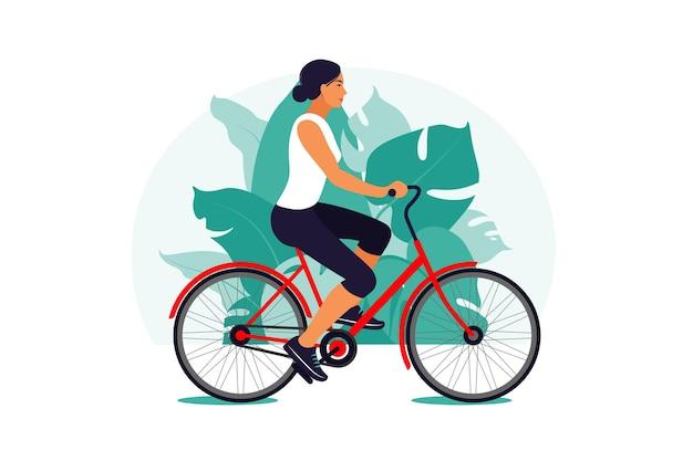 Kobieta na rowerze w parku. pojęcie zdrowego stylu życia. trening sportowy. zdatność.