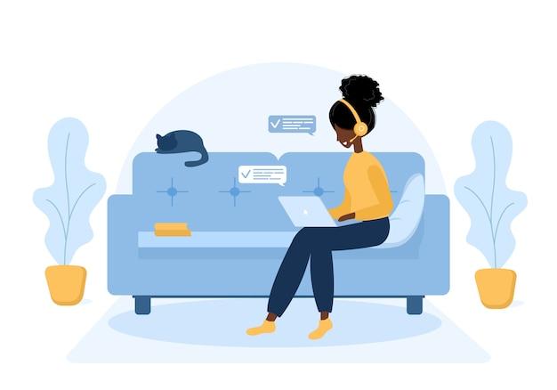 Kobieta na własny rachunek. afrykańska dziewczyna w słuchawkach z laptopem siedząc na kanapie. ilustracja koncepcja pracy, edukacji online, pracy z domu, zdrowego stylu życia. ilustracja w stylu płaski.