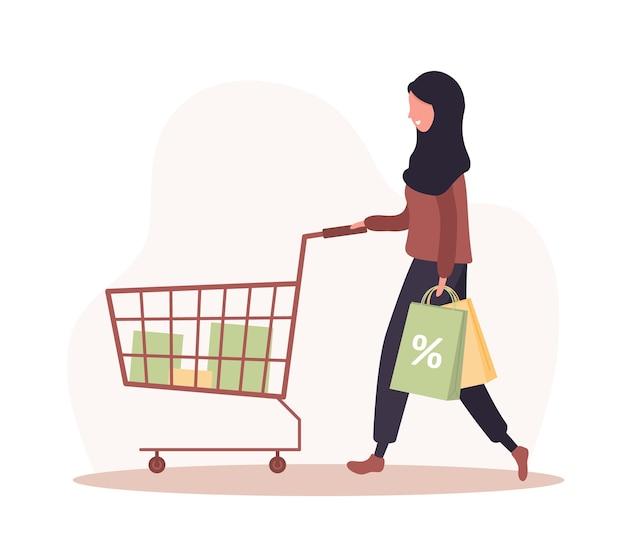 Kobieta na zakupy. szczęśliwa arabska dziewczyna z wózkiem i torbami.