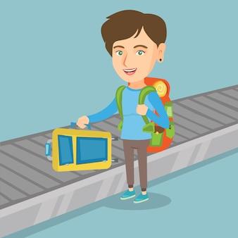 Kobieta odbiera walizkę z przenośnika taśmowego.