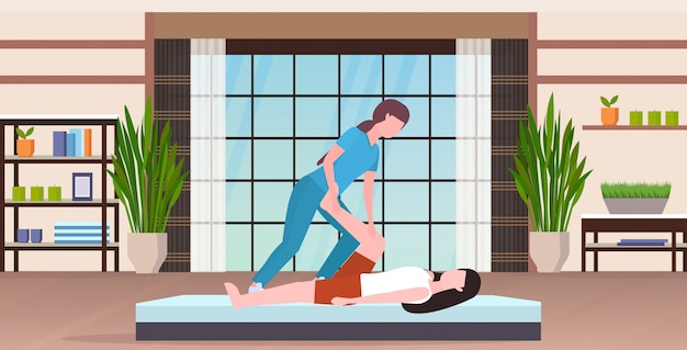 Kobieta osobisty trener robi ćwiczenia rozciągające z dziewczyną instruktor fitness, pomagając kobiecie rozciągnąć mięśnie treningu koncepcja nowoczesnej jogi studio siłowni wnętrze płaskie pełnej długości poziomej