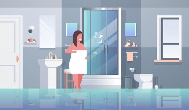 Kobieta owinięta białym ręcznikiem dziewczyna stoi w łazience po prysznic otyłości koncepcji