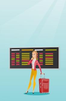 Kobieta patrząc na pokładzie odlotów na lotnisku.