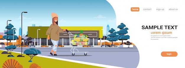 Kobieta pchanie wózka wózek z różnych słodkich owoców tropikalnych zdrowego stylu życia wegańskie jedzenie koncepcja nowoczesny supermarket budynku zewnętrzne poziome pełnej długości kopii przestrzeni
