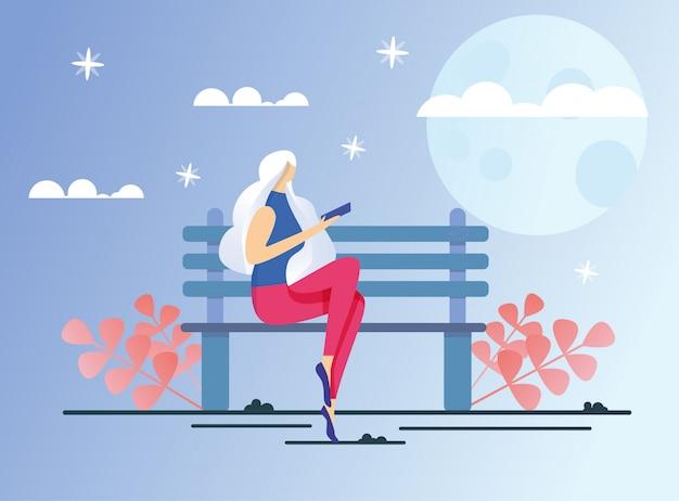 Kobieta pochłonięta czytaniem, siedząc na ławce w parku