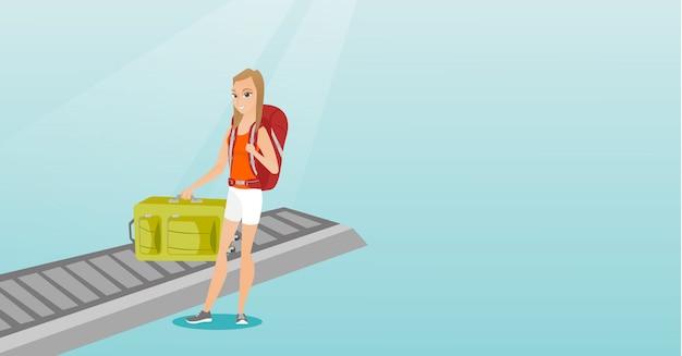 Kobieta podnosi walizkę z przenośnika taśmowego.