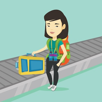 Kobieta podnoszenia walizki na pas przenośnika bagażu