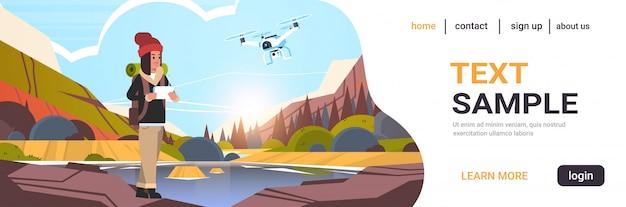 Kobieta podróżnik z plecakiem kontrolującym drona za pomocą zdalnego bloga podróżnego