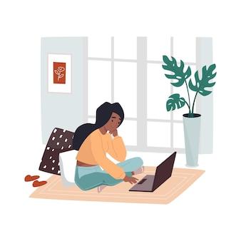 Kobieta pracująca w domu siedzi na podłodze w pobliżu notebooka dziewczyna w pracy w pokoju