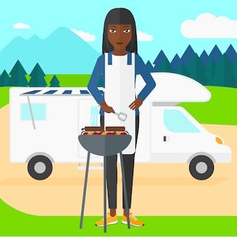 Kobieta przygotowuje grilla.