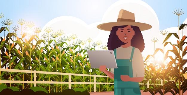 Kobieta rolnik z tabletem monitorującym stan pola kukurydzy wieśniaczka kontrolująca produkty rolne koncepcja inteligentnego rolnictwa krajobraz tło płaski poziomy portret