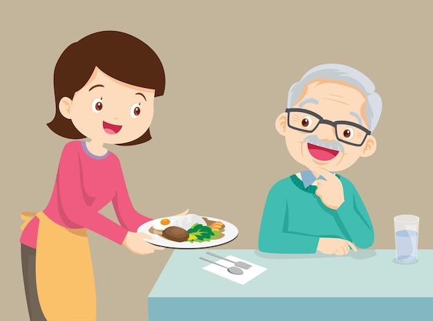 Kobieta serwująca jedzenie starszemu mężczyźnie