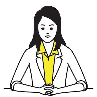 Kobieta siedząca przy stole, zaciśnięte dłonie z poważnym, zmartwionym, zestresowanym wyrazem twarzy.
