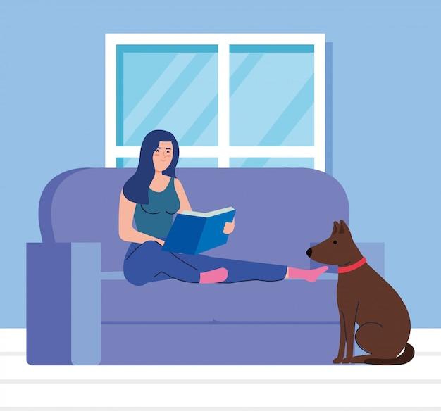 Kobieta siedzi na kanapie, czytając książkę, z maskotką psa