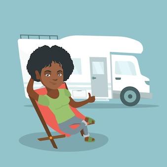 Kobieta siedzi na krześle przed samochód kempingowy.