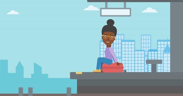 Kobieta siedzi na walizce na dworcu.