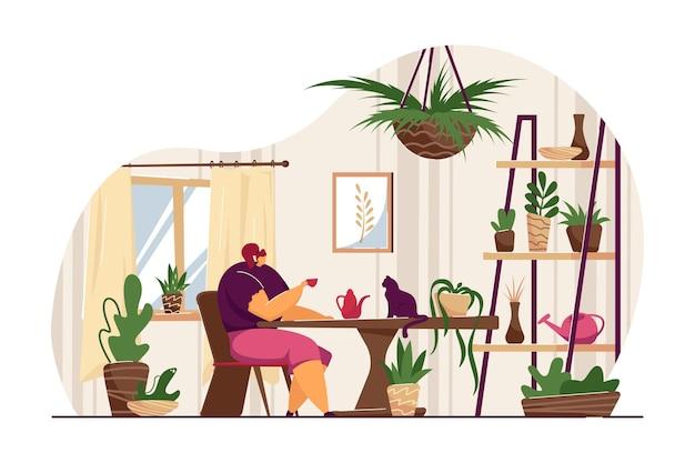 Kobieta siedzi przy stole z roślinami domowymi i kotem