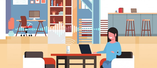 Kobieta siedzi w miejscu pracy z laptopem za pomocą inteligentnego inteligentnego głośnika z rozpoznawaniem głosu sztucznej inteligencji pomoc koncepcja nowoczesny obszar roboczy biuro wnętrze płaskie poziome portret
