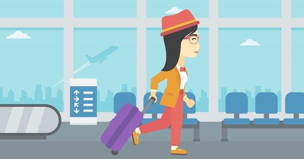 Kobieta spaceru z walizką na lotnisku.
