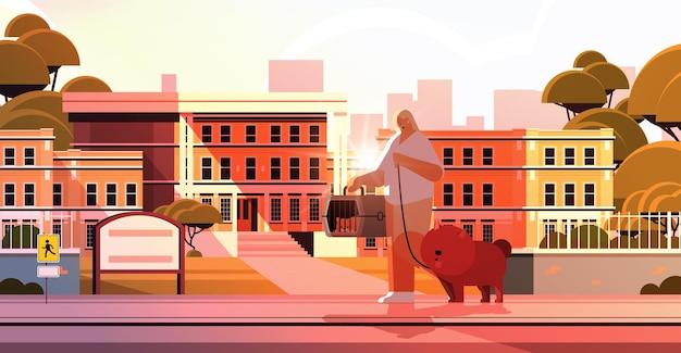 Kobieta spacerująca z psem i kotem właścicielką i uroczymi zwierzętami domowymi bawiącymi się przyjaźnią ze zwierzętami domowymi