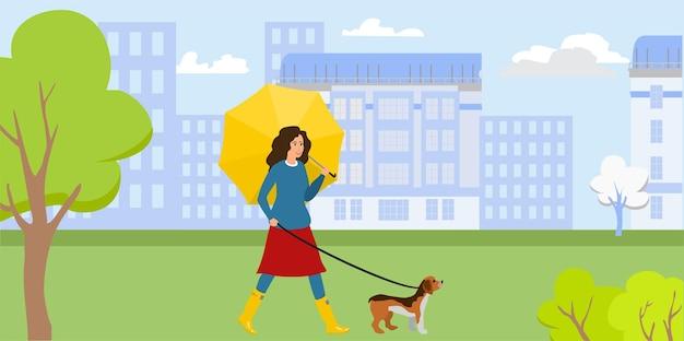 Kobieta spacerująca z psem w parku koncepcja aktywności na świeżym powietrzu wyprowadzanie psa w deszczu