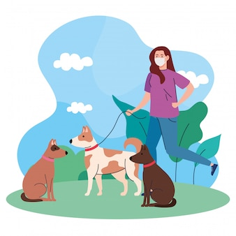 Kobieta spacerująca ze zwierzętami domowymi na zewnątrz, ubrana w maskę medyczną, przeciwko koronawirusowi covid 19