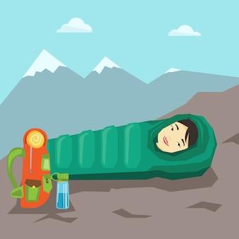 Kobieta śpi w śpiwór w górach.