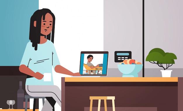 Kobieta spotykająca się z przyjaciółmi rasy mieszanej podczas kwarantanny koronawirusa pandemicznego podczas połączenia wideo