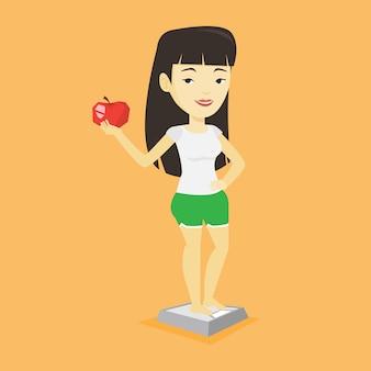 Kobieta stojąc na skali i trzymając jabłko w ręku.