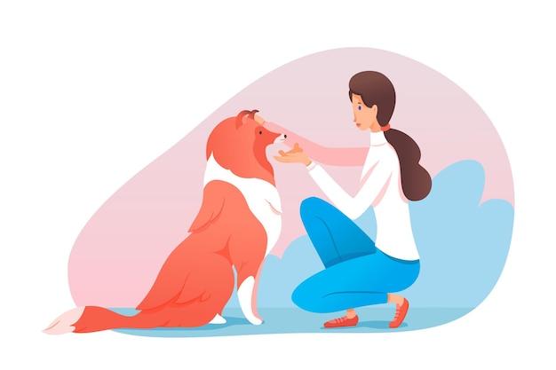 Kobieta trenerka traktuje psa rasy słodkim ciastkiem w kształcie kości dziewczyna chwaląc zwierzę domowe poklepane po głowie