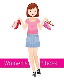 Kobieta trzyma buty. ona ma na sobie krótką spódniczkę dżinsową i tenisówki